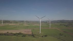 Flight near a wind power station in the daytime in the spring. Rotating blades of energy generators. Ecologically clean electricit. Y. Modern technologies for stock footage