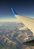 Plane wing over mountains. Flight over Alps somewhere between Switzerland and Austria Royalty Free Stock Photography