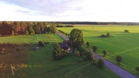 Flight over beautiful field and trees on background. Aerial rural landscape. Stunning aerial shot over lush green fields and meadows in the Estonian countryside stock footage