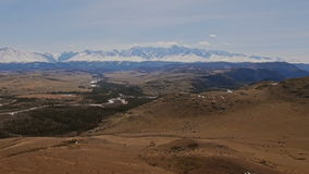 A flight over a beautiful valley with snowy mountains in the distance stock footage