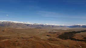 A flight over a beautiful valley with snowy mountains in the distance stock video footage