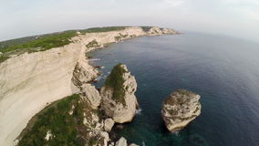 Flight over Bonifacio bay area at sunset colors. Rocks and sea. Corsica, France. Aerial view. stock video footage
