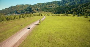 Flight over cars on a winding road in the hills and meadow. Rural highway below. stock video
