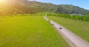 Flight over cars on a winding road in the hills and meadow. Rural highway below. stock footage