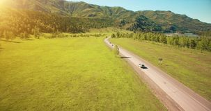 Flight over cars on a winding road in the hills and meadow. Rural highway below.