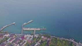 Flight over the city near the sea. Pier for ships.  stock video footage