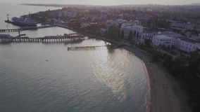 Flight over the city near the sea. Pier for ships.  stock video