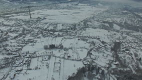 Flight over countryside village in winter at sunset, camera panning stock video footage