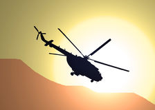 Flight over the desert. Illustration of silhouette of military helicopter MI-17 flying over the desert in the sunset Stock Photo