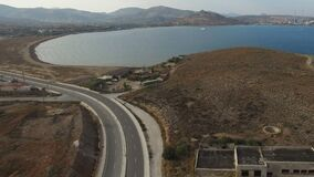 Empty curvy highway with lone car passing along the shore of Aegean Sea. Flight over empty curvy highway with lone car passing along the shore of Aegean Sea stock video footage