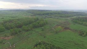 Flight over fields and meadows near the road. Aerial view. Flight over fields and meadows near the road, moving vehicles on road, small village outside city stock video footage
