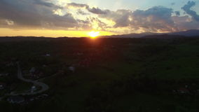 Flight over green hills and village against beautiful sunrise stock video footage