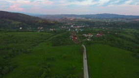 Flight over green hills and village against mountain range stock video footage