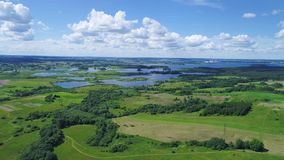 Flight over green meadows and blue sky land. Aerial view of green meadows and blue sky land stock video footage