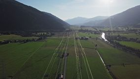 Aerial view of high voltage power line. Flight over of high voltage power line in mountain valley at sunset stock footage