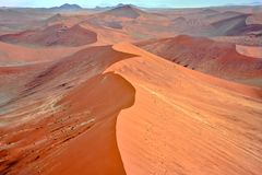 Flight over huge orange dunes in Namib Desert, Namibia. Aerial view of ridge of dunes. royalty free stock photos