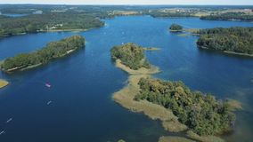 Flight over the lake with islands. Surroundings of Trakai castle, Lithuania. Beautiful aerial view in summer season. Flight over the lake with islands. Aerial stock video