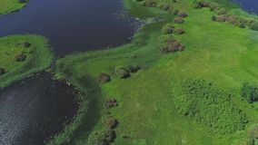 Flight over lakes and meadows land. Flight over blue lakes and green meadows land stock footage