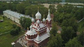 A flight over a modern brick church with golden domes stock video footage