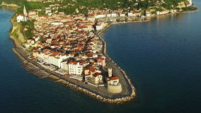 Flight over old city Piran, aerial panoramic view with old houses, roofs, St. George`s Parish Church, fortress and the sea. stock video footage