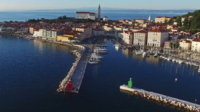 Flight over old city Piran, aerial panoramic view with old houses, St. George`s Parish Church, fortress, yachts, berths and sea. stock footage