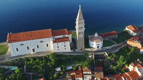 Flight over old city Piran in Slovenia, aerial bird`s eye view with old houses, St. George`s Parish Church and the sea stock video
