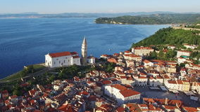 Flight over old city Piran in Slovenia, aerial panoramic view with old houses, St. George`s Parish Church and Tartini Square. stock video