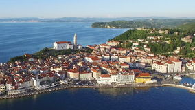 Flight over old city Piran in Slovenia, aerial panoramic view with old houses, St. George`s Parish Church and Tartini Square. stock footage