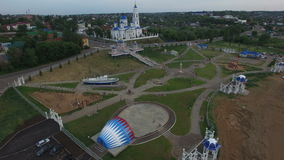 Flight over Park at Church with Stage and People Ride Bikes stock footage