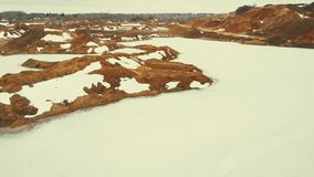 Flight over a quarry with frozen water lakes. The hills of sand and the icy surface of the water. The sad landscape of a frozen desert stock video footage