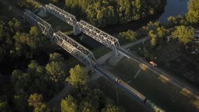 Passenger train goes over the bridge, filming from the top. Flight over the railway bridge on which the train is traveling - shooting with drones stock video footage