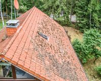 Flight over the red roof of a single family house with a chimney and a satellite antenna for inspection, control and preparation f. Or a repair, made with drone royalty free stock images