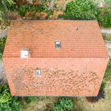Flight over the red roof of a single family house with a chimney and a satellite antenna for inspection, control and preparation f. Or a repair, made with drone royalty free stock photography
