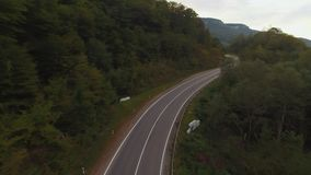 Flight over a rural landscape road following a car driving on it with lush green foliage, farming land. Aerial shot of a. Rural road with a car driving on it stock video