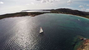 Flight over sea bay with rocks and yacht. Rondinara bay, Corsica, France. Aerial view. stock footage