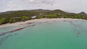 Flight over sea bay with surfers in France, Corsica, Santa Giulia beach. Aerial view. stock footage