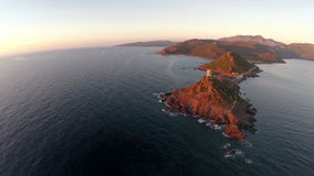 Flight over the sea and islands at sunset. Tour de la Parata, Ajaccio area, Corsica, France. Aerial view. stock footage