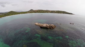 Flight over the sea with rocks and stones in water, Corsica, Santa Giulia beach. Aerial view. stock video footage