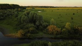 Flight over the Seim River, Ukraine surrounded by trees and meadows on its banks, view from the top - aerial videotaping stock footage