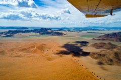 Namibia, flight over Sossusvlei. Border of orange dunes and rocks seen from plane, aerial view. View out of a plane over Namib-Naukluft National Park in Namibia Royalty Free Stock Image