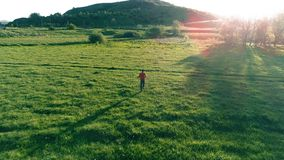 Flight over sport man at perfect green grass meadow. Sunset in mountain. UHD 4K aerial view. Low altitude flight over sport man at perfect green grass meadow stock footage