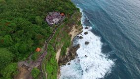 Flight over the Uluwatu temple along the rocky. Coast in Bali at cloudy day evening. Touristic place. Aerial footage of Bali, Indonesia stock video