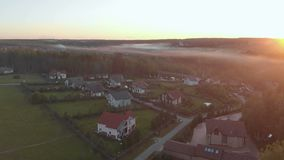 Flight over village with forest in sunrise soft light. Image processed in orange glow. Majestic landscape. Fog over the stock footage