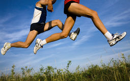 Flight of runners. Feet of runners  fly above earth background the blue sky Royalty Free Stock Photography