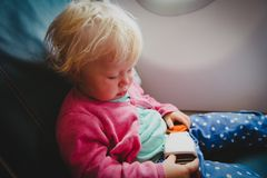 Flight safety - little girl fasten seat belt in plane. Flight safety - little baby girl fasten seat belt in plane stock photo