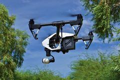 In Flight - Side View of Professional Camera Drone (UAV). Camera drone hovering at an R/C park between trees Royalty Free Stock Photo