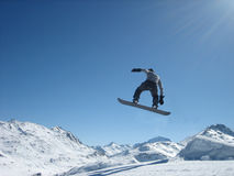 Flight on a snowboard. On a background of snow mountains Royalty Free Stock Photography