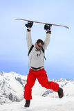 Flight with snowboard. Men jumps with snowboard in two hands Stock Photos