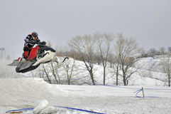 Flight on a snowmobile racer. On the snowmobile rider flies through the air against the backdrop of snow-capped mountains stock photography