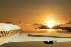 Flight in sunrise. Ahead future. Concept. Modern airplane is flying (taking-off, landing) in the morning sky with the sunrise on the background. The Royalty Free Stock Photo